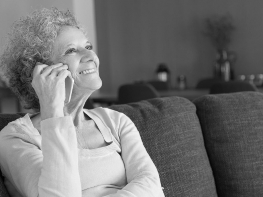 Close-up of happy senior woman talking on smartphone. Smiling grandmother sitting on couch at home and answering call. Elderly people and communication concept