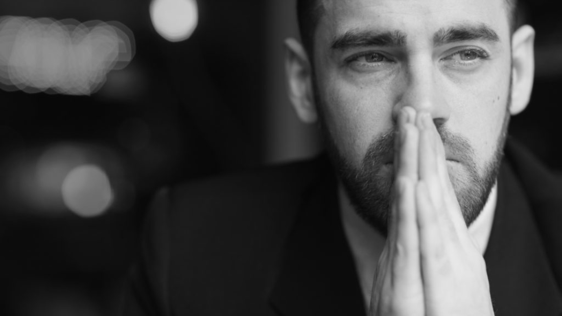 Portrait of modern bearded businessman looking away with red teary eyes, stressed and tired against black background, covering his mouth with hands