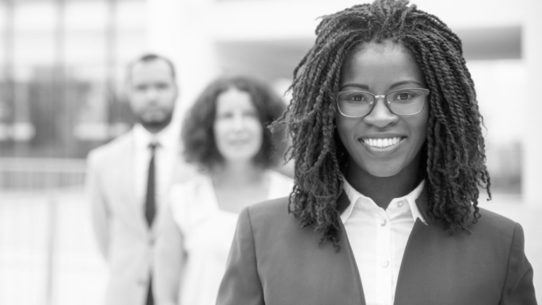 Cheerful young African American businesswoman. Portrait of confident female boss smiling at camera while standing with multiethnic colleagues, selective focus. Leadership concept