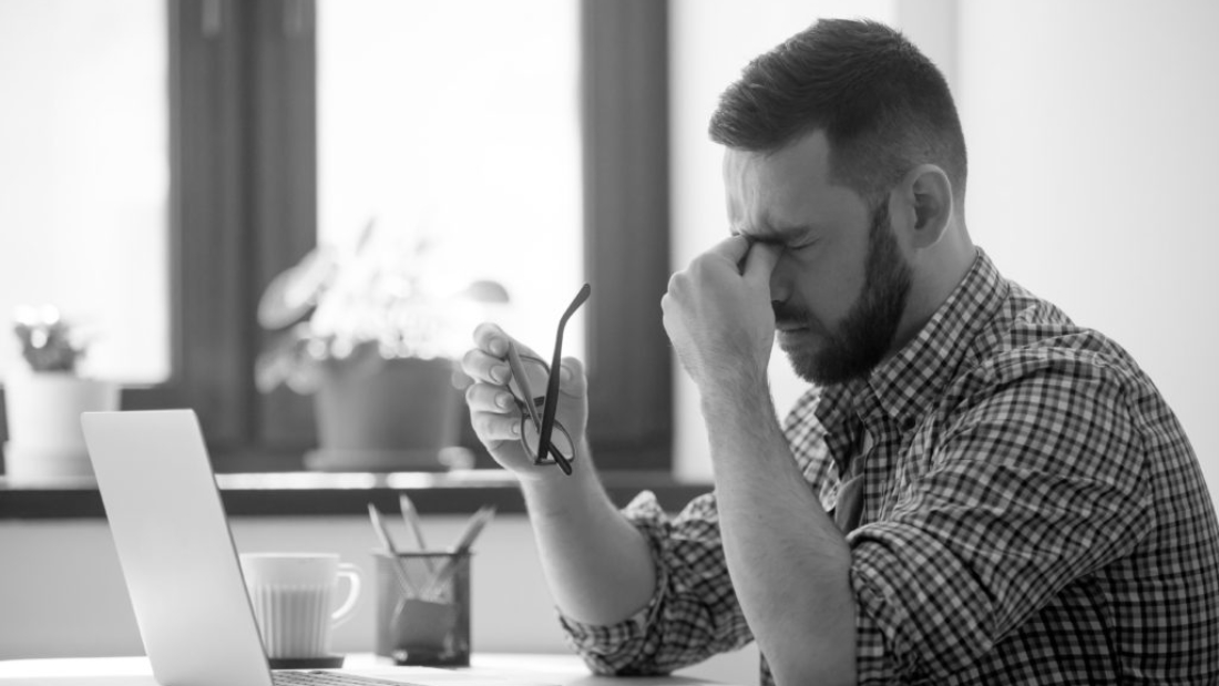 Tired stressed male worker taking off glasses, person massaging nose bridge suffering from headache and trying to relieve pain. Despaired man frustrated after reading company collapse or failure news